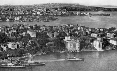 , Kirribilli is shown here from the top of the newly erected arch of the Sydney Harbour Bridge around 1932, just as it was being transformed by the construction of flats. 'Beulah Flats' is the large white waterfront building. It had been converted into a hotel in 1928. Stanton Library